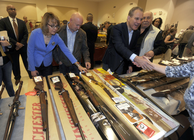 New York Attorney General Eric Schneiderman, right, former Arizona congresswoman Gabrielle Giffords, left, and her husband Mark Kelly, center, tour the New EastCoast Arms Collectors Associates arm ...