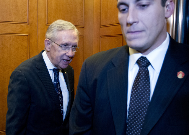 Senate Majority Leader Harry Reid of Nevada, left, comments to journalists as he takes the elevator after a rare Senate session  on Capitol Hill in  Washington, Sunday, Oct. 13, 2013. Senate Repub ...