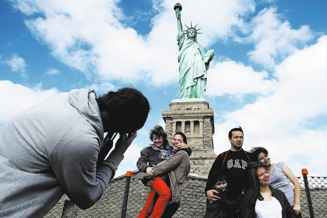 Tourists pose for photographs in front of the Statue of Liberty in New York Harbor, Sunday, Oct. 13, 2013, in New York. The Statue of Liberty reopened to the public after the state of New York agr ...
