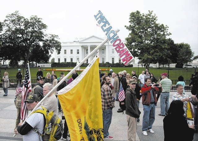 "A man, who asked to be identified only as ""Frank"", carries and ""Impeach Obama"" sign while protesting with others outside the White House in Washington Sunday, Oct. 13, 2013, as ..."