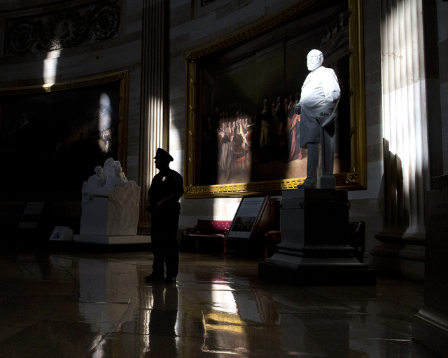 A Capitol Hill police officer stands in the Capitol Rotunda of the U.S. Capitol building on Monday, Oct. 14, 2013 in Washington. The federal government remains partially shut down and faces a firs ...