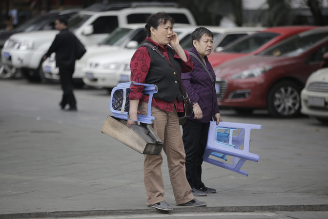 Two elderly shoe-shiners wait for customers at a park in Chongqing, China on March 19, 2013. With the worlds population aging faster than ever before, families and governments are struggling to de ...