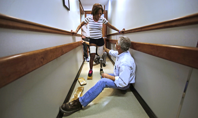 Paul Martino, of United Prosthetics, helps Mery Daniel as she takes her first step during a fitting for her prosthetic leg at the company in Boston on June 4 . Daniel lost most of her left leg in  ...