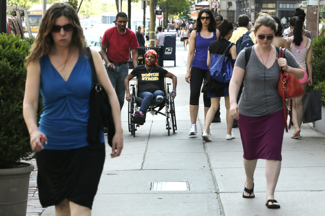 Mery Daniel, a Boston Marathon bombing survivor, rolls her wheelchair down Boylston Street in Boston on May 31 with her husband, Richardson Daniel, after visiting the explosion site where she lost ...