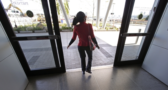Mery Daniel, a Boston Marathon bombing survivor, walks out the front door of Spaulding Rehabilitation Hospital following a physical therapy session on Sept. 27 in Boston. Daniel, whose heart stopp ...