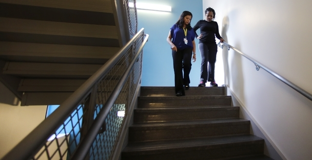 Mery Daniel, a Boston Marathon bombing survivor who lost most of her left leg, steadies herself as she climbs up and down stairs with her therapist Urvashi Chogle, left, at Spaulding Rehabilitatio ...