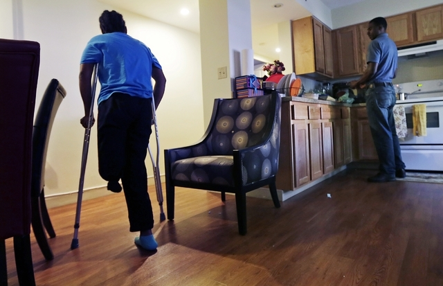 Mery Daniel, a Boston Marathon bombing survivor, uses crutches on June 20 as she heads down a hallway in her home in the South End neighborhood of Boston, while husband Richardson Daniel helps pre ...