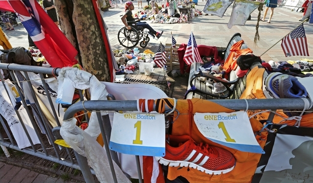 Mery Daniel, a Boston Marathon bombing survivor, rolls her wheelchair through a memorial for victims and survivors of the blast on May 31 at Copley Square near the race's finish line in Boston. At ...