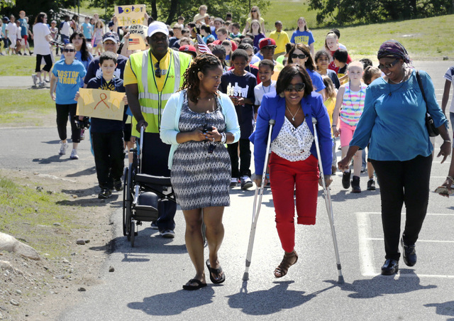 Mery Daniel, a Boston Marathon bombing survivor, uses borrowed crutches as she walks with students during a fundraising walkathon for her on June 5 at the William Seach Primary School in Weymouth, ...