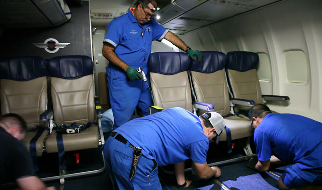 Southwest Airlines aircraft technicians install newer, skinnier seats on a 737 at the carrier's headquarters in Dallas. Southwest says passengers will have the same amount of legroom even though t ...