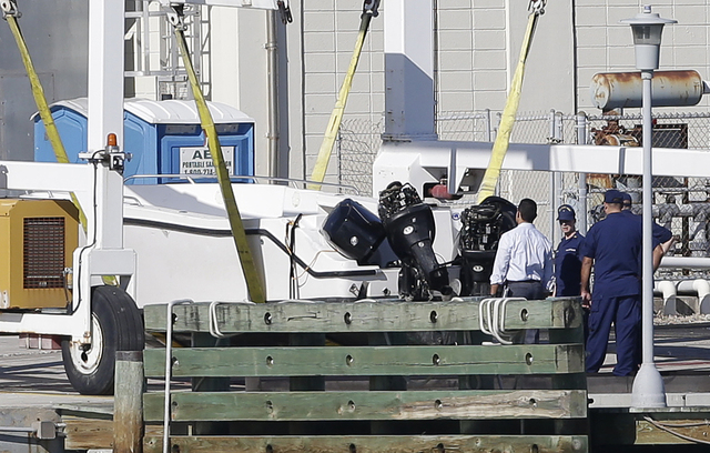 Members of the U.S. Coast Guard examine a small white boat Wednesday at the U.S. Coast Guard Station Miami Beach in Florida. Four women died and 11 people were taken into custody after the boat wi ...
