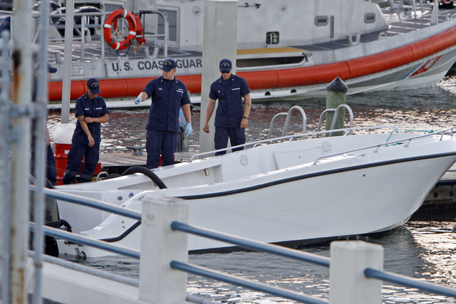 U.S Coast Guard personnel inspects a vessel with a missing center console that capsized near Miami on Wednesday. The Coast Guard responded to an early morning call and found nine people clinging t ...