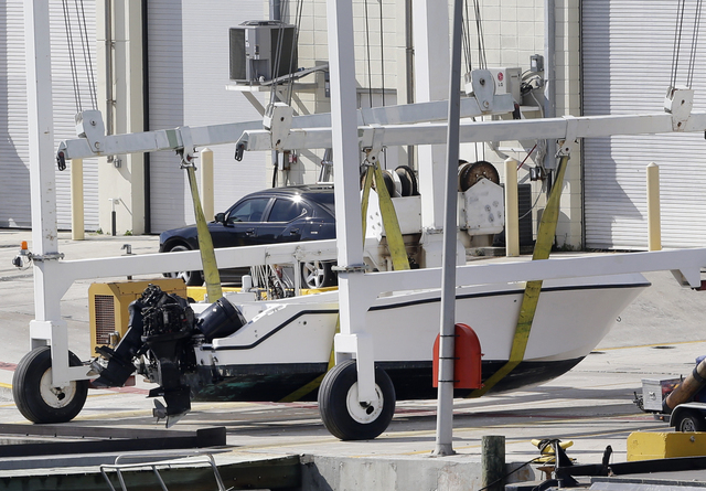 A small white boat with its center console missing sits on the dock after authorities lifted it out of the water Wednesday at the U.S. Coast Guard Station Miami Beach in Florida. Four women died a ...