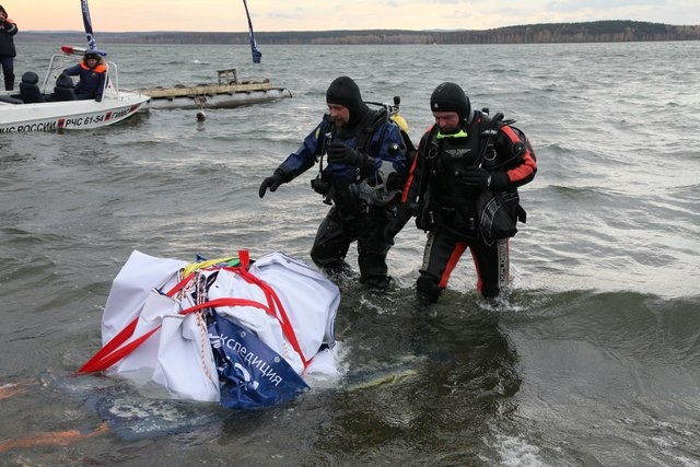 Divers retrieve what is believed to be part of the Chelyabinsk meteor from Chebarkul Lake near Chelyabinsk, some 1500 kilometers (930 miles) east of Moscow, Russia,  Wednesday, Oct. 16, 2013. Scie ...