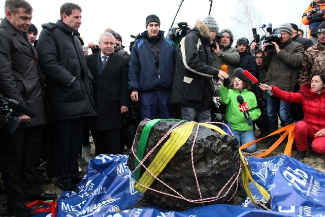 People look at what scientists believe to be a chunk of the Chelyabinsk meteor, recovered from Chebarkul Lake near Chelyabinsk, about 1500 kilometers (930 miles) east of Moscow,  Russia, Wednesday ...