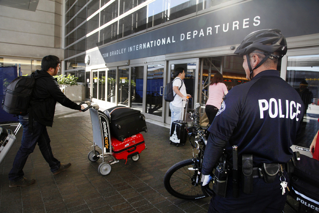 A Los Angeles Police officer patrols outside the departure area at Los Angeles International Airport on Wednesday, Oct. 16, 2013. Police at Los Angeles International Airport are continuing their s ...