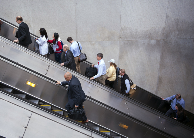People exit a Metro subway station, by escalator, along Pennsylvania Ave., NW, in Washington, Thursday. After 16 days of being off the job, thousands of furloughed federal workers are returning to ...
