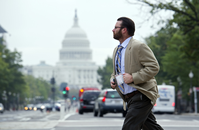 A man crosses Pennsylvania Ave., NW, in front of the Justice Department, in Washington on Thursday. After 16 days of being off the job, thousands of furloughed federal workers are returning to wor ...