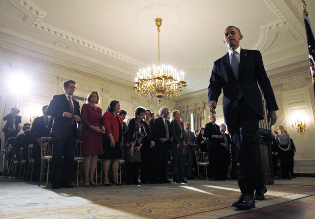 An audience comprising of White House staff members, stands as President Barack Obama leaves the State Dining Room of the White House on Thursday after he made a statement. (AP Photo/Charles Dharapak)