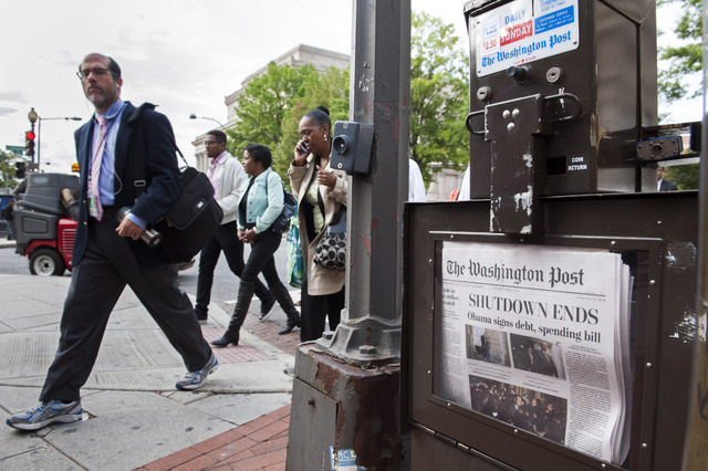 People pass a Washington Post newspaper box as they head to work near Pennsylvania Ave., NW, in Washington on Thursday. After 16 days of being off the job, thousands of furloughed federal workers  ...
