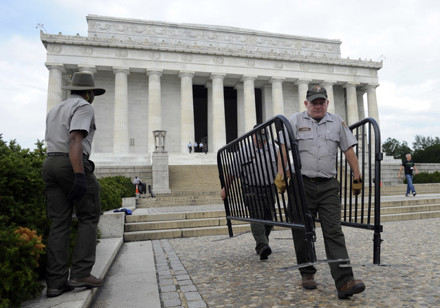 National Park Service employee James Mitchell, right, and others, remove barricades from the grounds of the Lincoln Memorial in Washington on Thursday. Barriers went down at National Park Service  ...