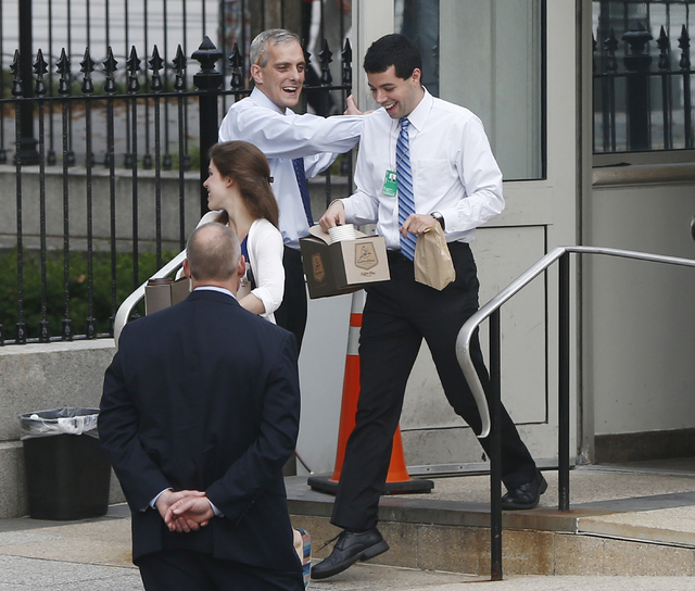 White House Chief of Staff Denis McDonough, center, greets federal employees at the entrance to the Eisenhower Executive Office Building as he they return to the White House in Washington on Thurs ...