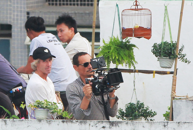 "American film director Michael Bay, left, assists the cameraman as they are filming their latest film ""Transformers Four"" in Hong Kong Thursday, Oct. 17, 2013. Two men have been arrested ..."