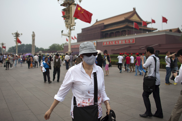 A foreign tourist wearing a mask walks in front of Tiananmen Gate on a polluted day in Beijing, China, in this May 7, 2013 file photo.  What many commuters choking on smog have long suspected has  ...