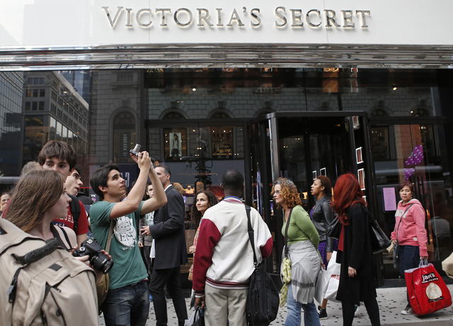 A tourist pauses to snap a photograph in front of the Victoria's Secret Herald Square store in midtown Manhattan, Thursday, Oct. 17, 2013, in New York. A security guard on the lookout for shoplift ...