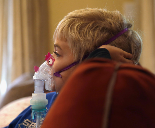 Carter Howard sits and watches a cartoon during his asthma treatment at his home in Northbrook, Ill. (AP Photo/Charles Rex Arbogast)
