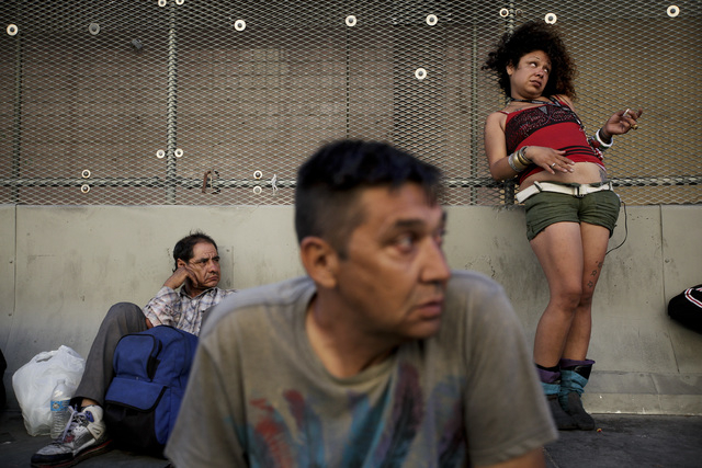 George Mendez, foreground, a 55-year-old recovering alcoholic, sits in front of a drunk woman in the Skid Row area of Los Angeles on Tuesday, July 23, 2013.  (AP Photo/Jae C. Hong)