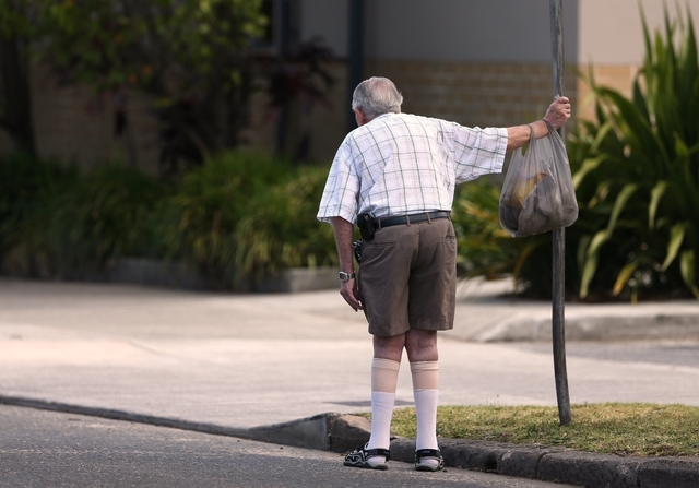 In this Friday, Oct. 11, 2013 photo, an elderly man holds onto a signpost on the side of a road in Sydney. About a third of people over 65 fall every year, according to the World Health Organizati ...