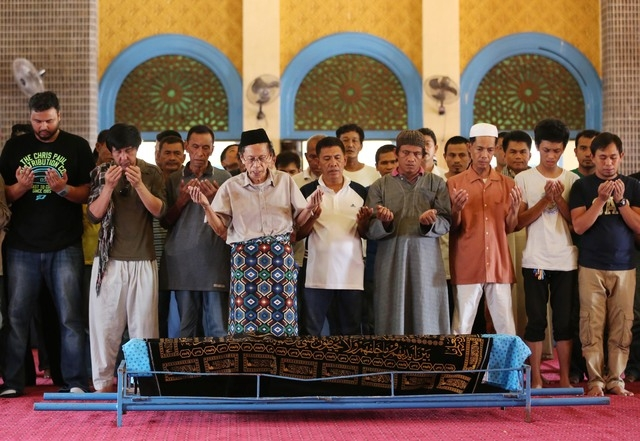 Relatives and followers pray beside the coffin of Filipino Sultan Jamalul Kiram III at the Blue Mosque in Maharlika village in Taguig city, south of Manila, Philippines on Sunday, Oct. 20, 2013. K ...