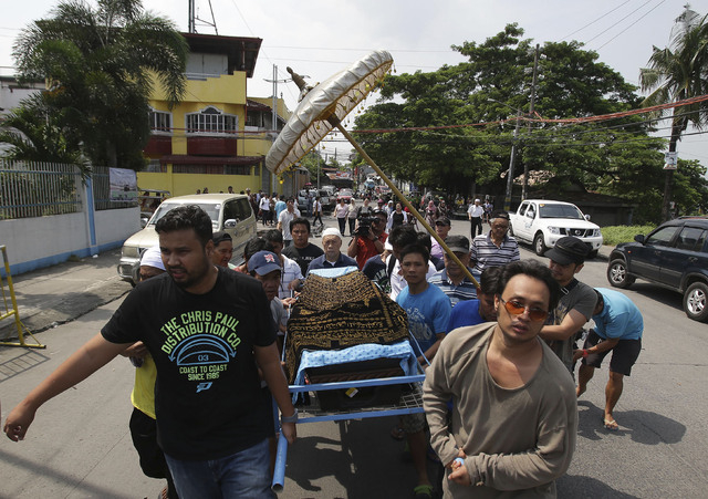 Relatives and followers carry the coffin of Filipino Sultan Jamalul Kiram III towards the Blue Mosque in Maharlika village, Taguig city, south of Manila, Philippines on Sunday, Oct. 20, 2013. Kira ...