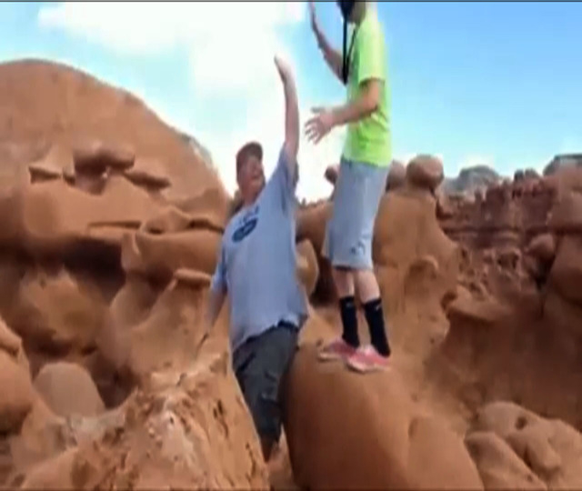 This frame grab from a video taken by Dave Hall shows  two men cheering after a Boy Scouts leader knocked over an ancient Utah desert rock formation at Goblin Valley State Park. Authorities are mu ...