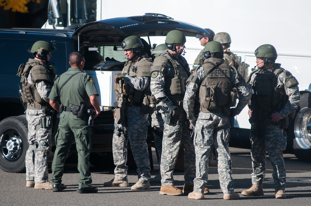 Swat team members secure the scene near Sparks Middle School in Sparks, Nev., after a shooting there on Monday, Oct. 21, 2013.  Authorities are reporting that two people were killed and two wounde ...