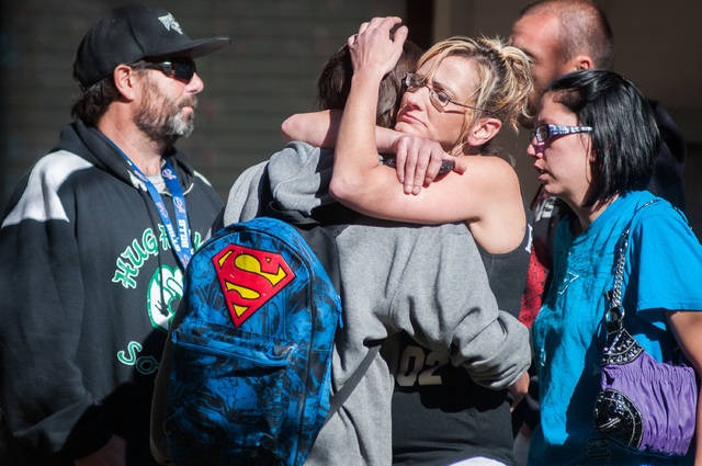 A Sparks Middle School student, back to camera, cries with family members after being released from Agnes Risley Elementary School Monday Oct. 21, 2013, in Sparks Nev., after a shooting at Sparks  ...