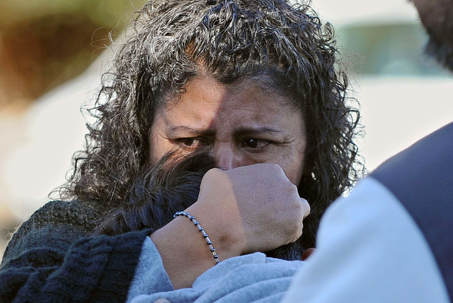 A unidentified woman holds her son after picking him up at Sparks high school were some students where taken after a shooting that left two dead at Sparks Middle School on Oct. 21, 2013. Police sa ...