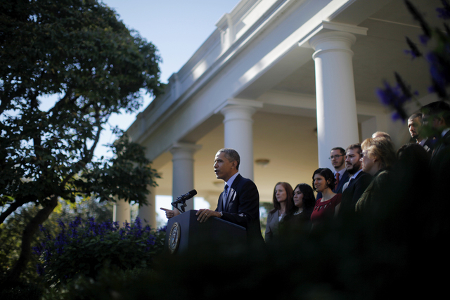 President Barack Obama, standing with supporters of his health care law, speaks in the Rose Garden of the White House in Washington, Monday, Oct. 21, 2013, on the initial rollout of the health car ...