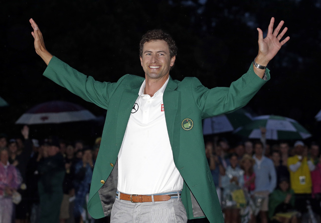 FILE - In this April 14, 2013 file photo, Adam Scott, of Australia, celebrates with his green jacket after winning the Masters golf tournament in Augusta, Ga. Scott considers his 20-foot birdie pu ...