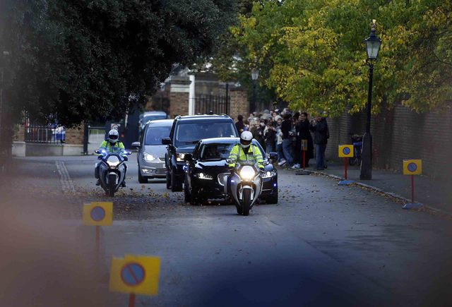The car carrying Britain's Prince William, the Duchess of Cambridge and their son, Prince George, is escorted by police as it drives from Kensington Palace on the way to St. James Palace for the c ...
