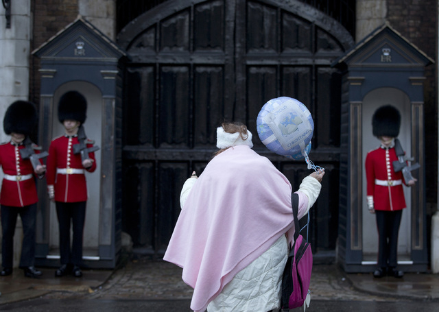 A royal fan holding a christening celebration balloon watches as members of the Grenadier Guards mount guard outside St. James's Palace in London on Wednesday. Britain's Prince George, son of Prin ...