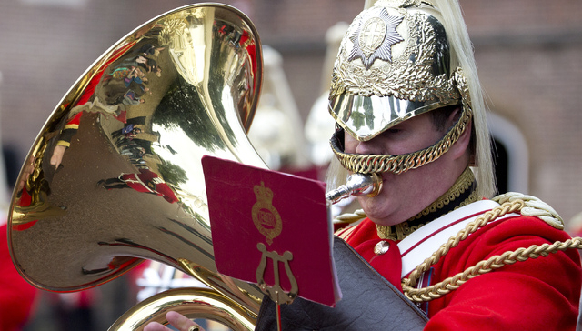 Tourists are reflected in the brass of a member of the Life Guards band as they escort a Colour party of the Grenadier Guards as they leave St. James's Palace to change the guard at Buckingham Pal ...