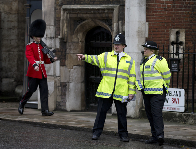Police officers monitor the small crowd of media and royal fans outside St. James's Palace as a member of the Grenadier Guards marches past in London on Wednesday. Queen Elizabeth II and her husba ...