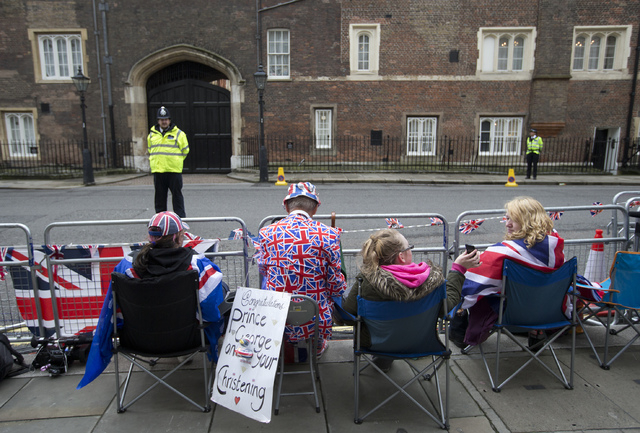 Royal fans wait outside St. James's Palace Wednesday in the hopes of catching a glimpse of members of the British royal family who will be attending the christening of Prince George in London.  (A ...