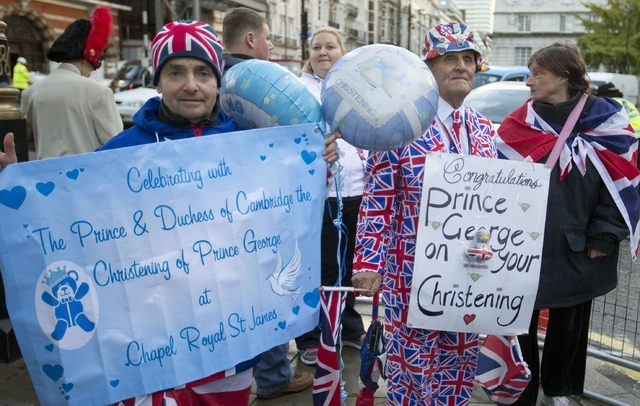 Royal wellwishers gather and display their home made placards and greetings to the media,  as they wait outside St James's Palace, for the christening of Britain's Prince George, in London, Wednes ...