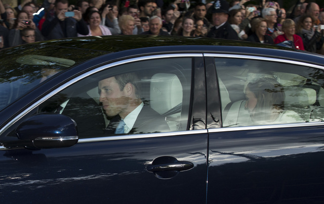Britain's Prince William, left, and his wife Kate the Duchess of Cambridge, right, arrive for the christening of their son, Prince George, at St. James's Palace in London on Wednesday.  (AP Photo/ ...