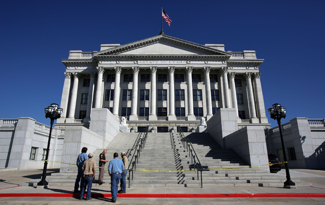People gather at the base of the steps leading to the west entrance to the Utah State Capitol in Salt Lake City Tuesday Oct. 22, 2013, after a man drove a pickup truck up the steps to the entrance ...