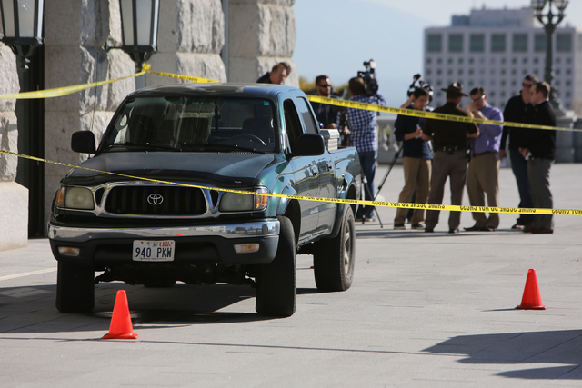 The pickup truck driven up several flights of steps to the west entrance of the Utah State Capitol in Salt Lake City Tuesday Oct. 22, 2013, sits behind crime scene tape.  Utah state troopers used  ...