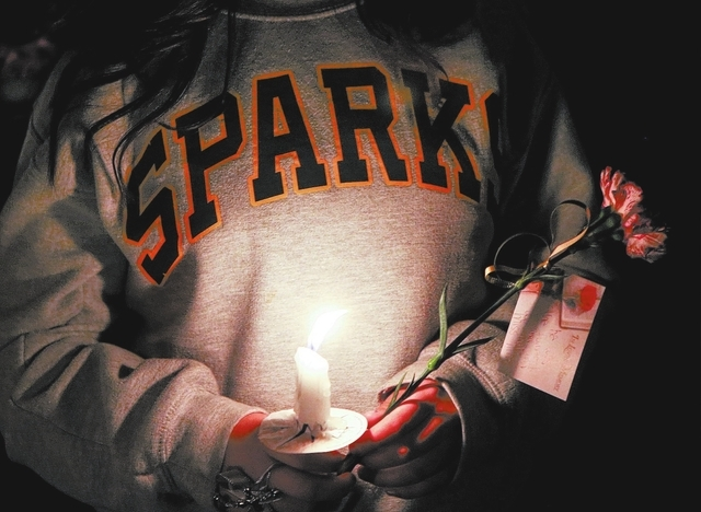 Hundreds of students and residents attend a candlelight vigil at Sparks Middle School in Sparks, Nev., on Wednesday, Oct. 23, 2013, in honor of slain teacher Michael Landsberry and two 12-year-old ...